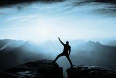 Crazy hiker in black is jumping between rocky peaks. Risking man. Wonderful daybreak. Flare, soft focus. Crazy hiker in black is jumping between rocky peaks Royalty Free Stock Photos