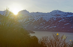 Flaring sun rising behind Eiger peak in Jungfrau region of Switz Stock Photography