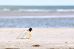 Flasche auf einem Sandstrand Stockfotos
