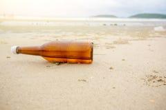 Flasche auf Strandmeer und -himmel vom Meer ausgespülte Flasche auf dem Strand lizenzfreie stockbilder