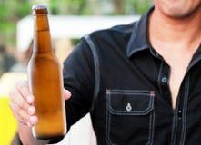 Flasche Bier in der Hand Stockfotografie