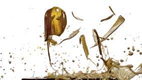 Flasche Bier fallend, brechend und auf Stahlplatte gegen weißen Hintergrund spritzend stock footage