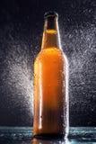 Flasche Bier gespritzt mit Wasser Lizenzfreies Stockfoto