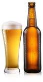 Flasche Bier mit Tropfen auf Weiß. Lizenzfreie Stockfotografie