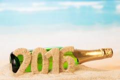 Flasche Champagner mit Aufschrift 2016 auf Sand Stockfotos