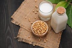 Flasche der Sojamilch und der Sojabohne auf Holztisch Lizenzfreies Stockfoto