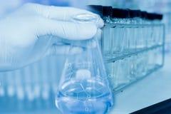 Flasche in der Wissenschaftlerhand mit Reagenzgläsern Lizenzfreie Stockfotografie