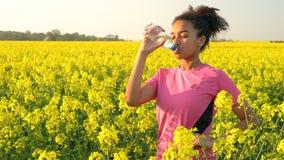 Flasche des laufenden und Trinkwassers des Jugendlichen auf dem Gebiet von gelben Blumen stock footage