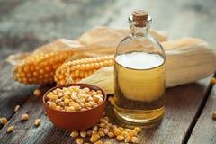Flasche des Maisätherischen öls, Samen in der Schüssel und Maiskolben Stockfoto