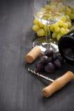 Flasche des Rotweins, der Traube und des Korkenziehers auf einem hölzernen Hintergrund Stockbild