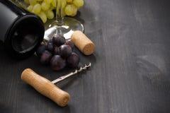 Flasche des Rotweins, der Traube und des Korkenziehers auf einem hölzernen Hintergrund Stockfoto