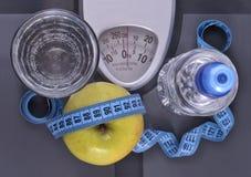 Flasche des Wassers, des grünen Apfels, des Glases Wassers und des messenden Bands Stockfotos