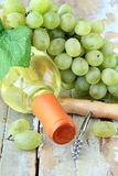 Flasche des weißen Weins, der Trauben und des Korkenziehers Stockfotos
