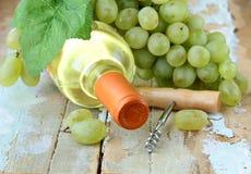 Flasche des weißen Weins, der Trauben und des Korkenziehers Lizenzfreies Stockbild