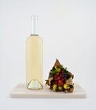 Flasche des weißen Weins und Herbstblumenstrauß Stockfotografie