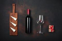 Flasche des Weins, der Geschenkbox, des blauen stinky Käses und des Weinglases auf rostigem Hintergrund Lizenzfreies Stockfoto