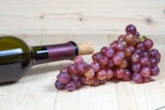 Flasche des Weins und der Traube auf hölzernem Stockbilder