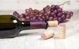 Flasche des Weins und der Traube auf hölzernem Stockfotografie