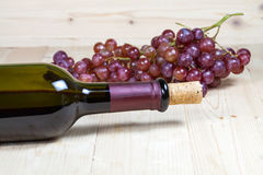 Flasche des Weins und der Traube auf hölzernem Stockbild