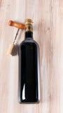 Flasche des Weins und des Korkenziehers über hölzernem Hintergrund Lizenzfreie Stockbilder