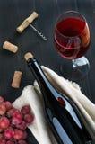 Flasche des Weins, des Weinglases, der Trauben und des Korkenziehers auf dunklem Hintergrund lizenzfreies stockbild