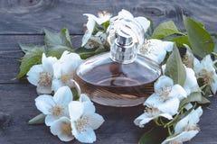 Flasche Jasminblumen auf hölzernem Hintergrund Duftendes Parfüm des Jasmins stockbild