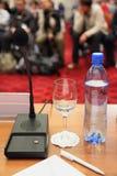 Flasche, Mikrofon, Glas und Feder auf Tabelle Lizenzfreies Stockfoto