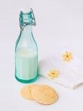 Flasche Milch, Butterplätzchen, Blumen Stockbilder