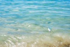 Flasche mit der Mitteilung, die auf das Wasser schwimmt Stockfotografie