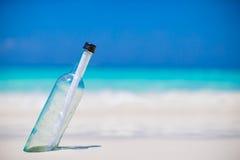 Flasche mit einer Mitteilung begraben im weißen Sand lizenzfreies stockbild