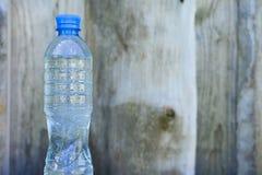 Flasche mit frischem Trinkwasser auf unscharfem h?lzernem Wandhintergrund lizenzfreie stockfotos