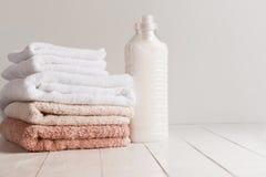 Flasche mit Gel für das Waschen und ein Stapel frische Tücher auf einem Holztisch Stockbild