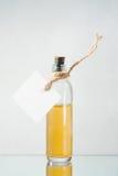 Flasche mit gelber Flüssigkeit und leeren Aufkleber auf dem hellen backgroun Stockfoto
