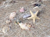 Flasche mit Meldung im Fischernetz stockbild