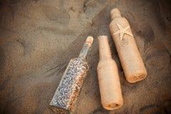 Flasche mit Oberteilen auf dem Sand Stockfotografie
