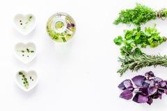 Flasche mit organischem Öl mit Krautbestandteilen auf weißem Draufsichtmodell des Hintergrundes stockfotos