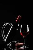 Flasche mit Rotwein auf einem Standplatz und einem Glas Lizenzfreie Stockbilder