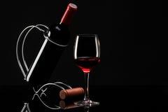 Flasche mit Rotwein auf einem Standplatz und einem Glas Stockfotografie
