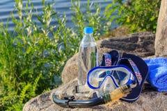 Flasche mit Wasser, Tuch, Flipflops, Maske für das Tauchen und snork Lizenzfreies Stockbild