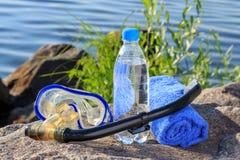 Flasche mit Wasser, Tuch, Maske für das Tauchen und Schnorchelrohr auf r Stockfotografie