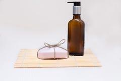 Flasche mit Zufuhr und ein Stück rosa Seife auf einer weißen Tabelle Lizenzfreie Stockfotos
