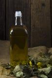 Flasche Olivenöl auf einem trockenen grünen Laub auf einem Hintergrund von VI Lizenzfreies Stockbild