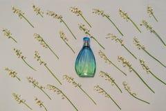 Flasche Parfüm- und Maiglöckchenblumen auf hellem Pastellhintergrund Parfümerie, Duft, kosmetisches Konzept Frühling oder stockfotografie