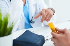Flasche Pillen in den Händen der geduldigen Nahaufnahme Männlicher gestikulierender Doktor erklärt, wie man die Droge in nimmt lizenzfreie stockfotos