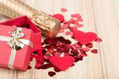 Flasche Rebe, rote Herzen und Mitbringsel Lizenzfreies Stockfoto