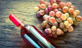 Flasche rosafarbener Wein mit Weintraube Stockfotografie