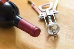 Flasche Rotwein mit einem Korkenzieher Lizenzfreies Stockfoto