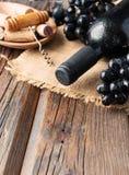 Flasche Rotwein mit frischer Traube und Bündel Korken auf Holztisch stockfoto