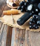 Flasche Rotwein mit frischer Traube und Bündel Korken auf Holztisch stockbild