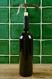 Flasche Rotwein mit Korkenzieher über grünem Hintergrund Lizenzfreies Stockfoto